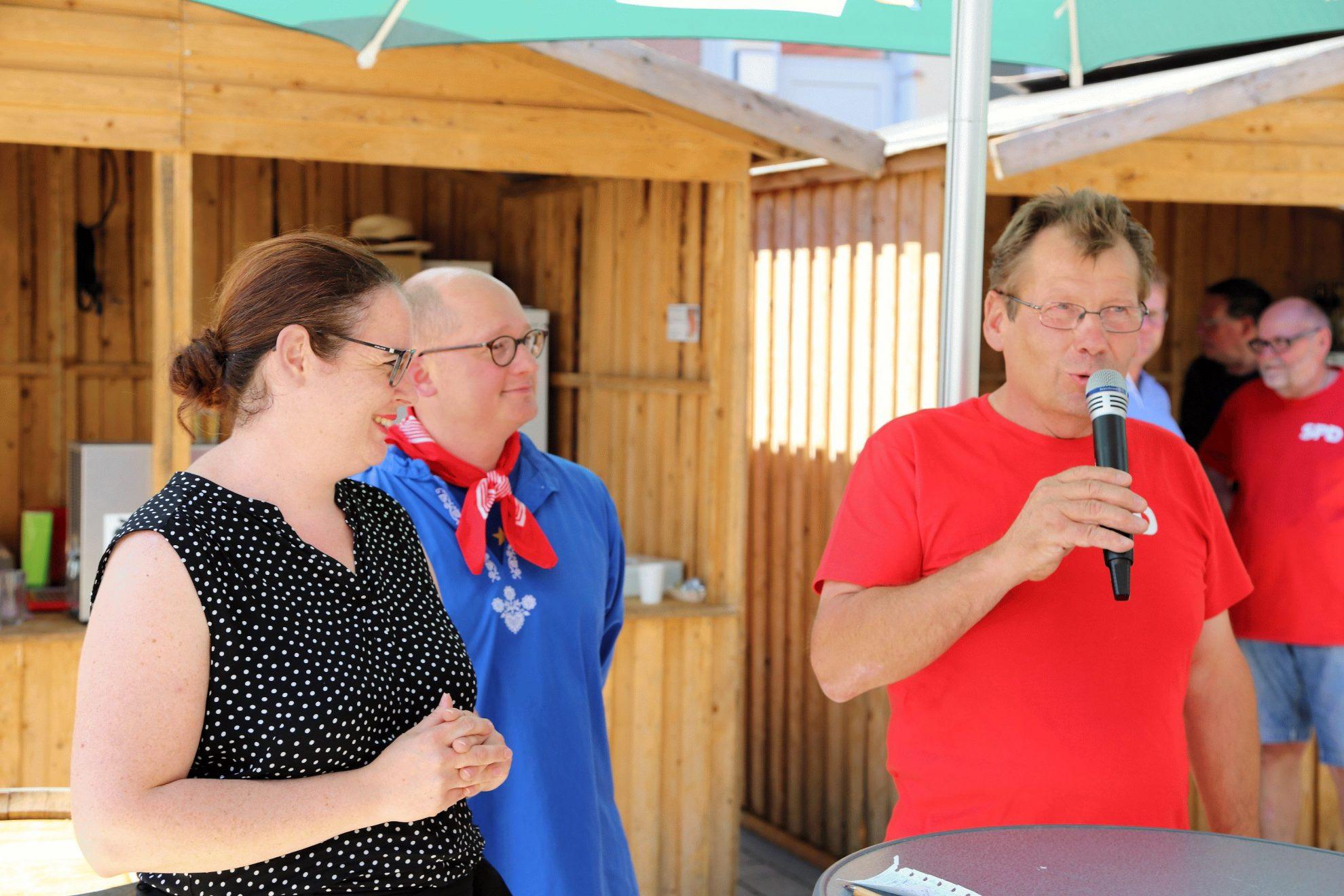 von links nach rechts, Lisa Gnadl, Rouven Kötter und Karl-Otto Waas begrüßen die Gäste, sommerlich gekleidet an Stehtischen, Karl-Otto Waas mit Mikrofon