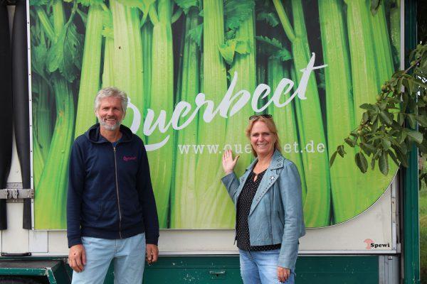 Thomas Wolff, Geschäftsführer von Querbeet, mit Erster Kreisbeigeordneter Stephanie Becker-Bösch, stehend vor Fahrzeug mit großflächiger Querbeet Werbung mit Staudensellerie als Motiv
