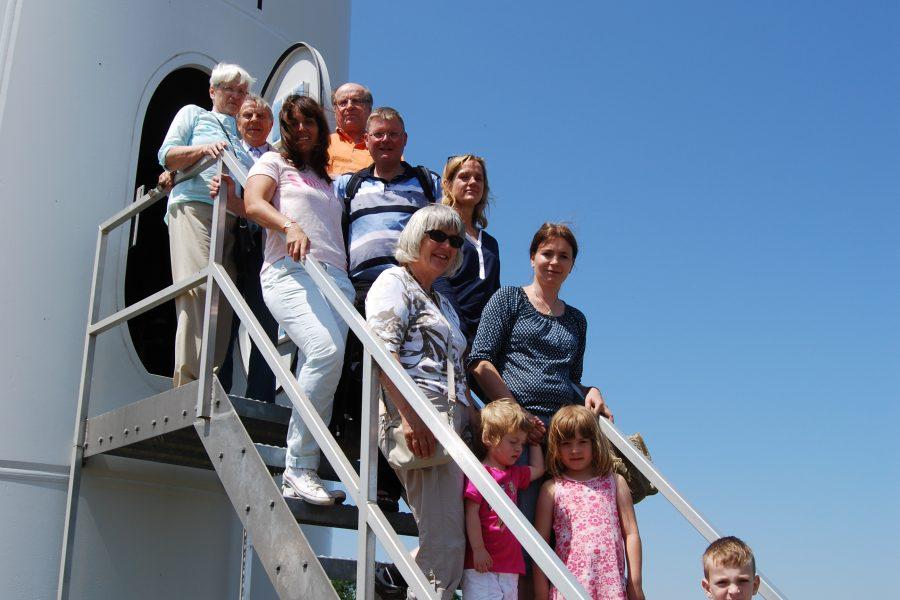 Besuchergruppe auf der Treppe vor dem Eingang einer der Anlagen in Kloppenheim bei sommerlichen Temperaturen.