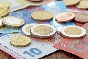 Banknoten und Münzen auf einem Holztisch als Illustration
