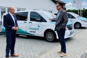 Rouven Kötter (links) bei der Hopper-Zentrale in Mainhausen mit dem dortigen Kreistagsabgeordneten Kai Gerfelder (SPD). Zwei Fahrzeuge der Hopper Flotte im Hintergrund
